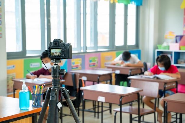 Grupo de crianças da escola com o professor que senta-se na sala de aula em linha e que levanta as mãos, escola primária, aprendizagem e conceito dos povos, aprendizagem e conceito dos povos, distanciamento social.