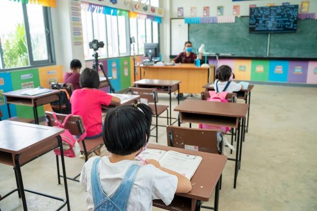 Grupo de crianças da escola com o professor sentado na sala de aula na escola primária.