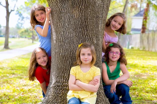 Grupo de crianças de irmãs meninas e amigos no tronco de árvore