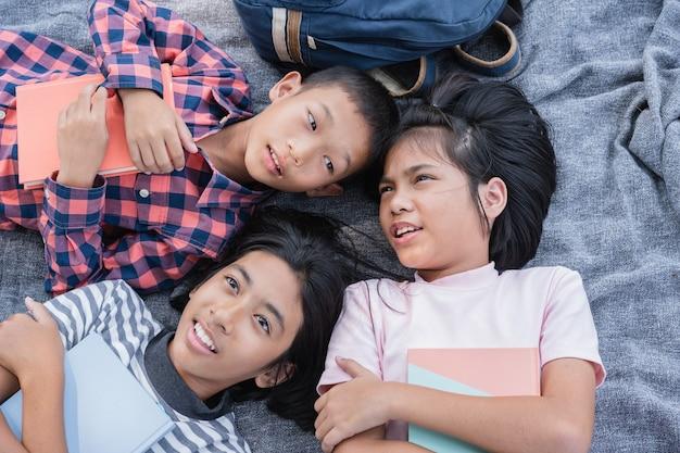 Grupo de crianças do ensino fundamental conversam deitados no cobertor