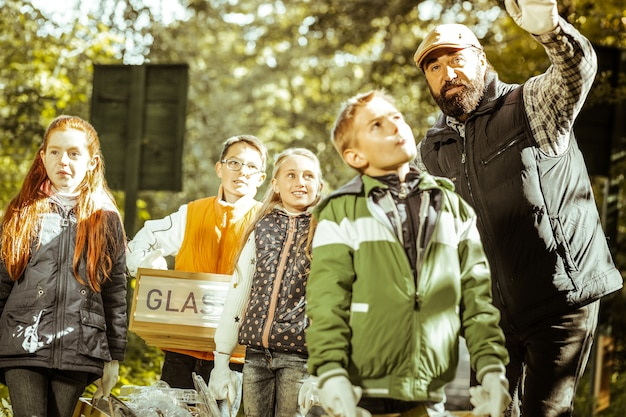 Grupo de crianças e professor recolhendo lixo e separando-o na floresta em um dia bom