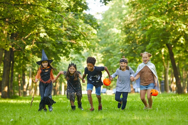 Grupo de crianças em fantasias de halloween correndo na grama verde do parque e se divertindo na festa