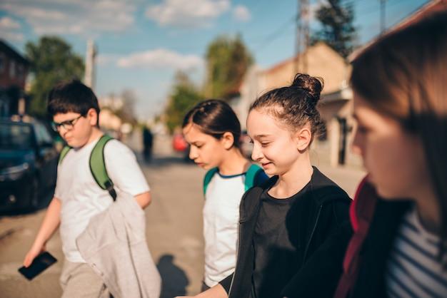 Grupo de crianças em idade escolar atravessando a estrada