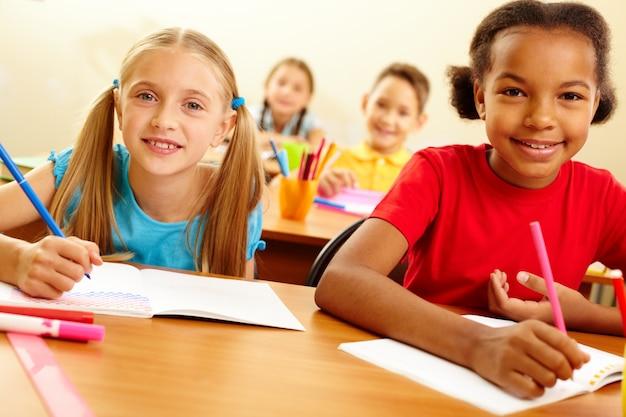 Grupo de crianças em idade escolar com lápis e cadernos na sala de aula