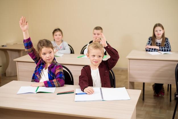 Grupo de crianças em idade escolar, sentado na sala de aula e levantando as mãos.