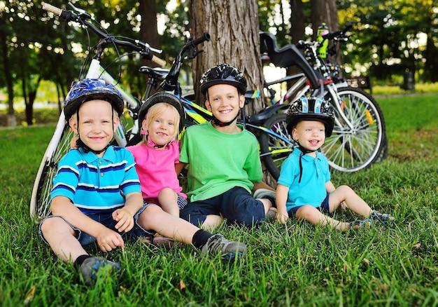 Grupo de crianças em idade pré-escolar com capacetes de segurança para bicicletas sorri sentados na grama verde fresca do parque, contra a superfície de bicicletas e árvores