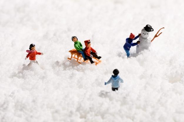 Grupo de crianças em miniatura brincando de trenó na neve ou tobogã e construindo um boneco de neve