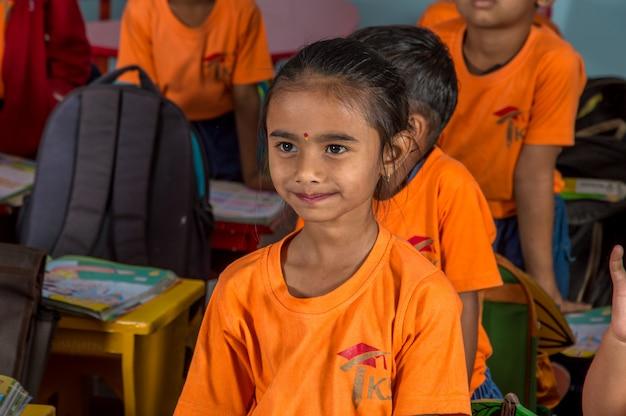 Grupo de crianças estudantes está cantando canções e dançando na sala de aula da escola.
