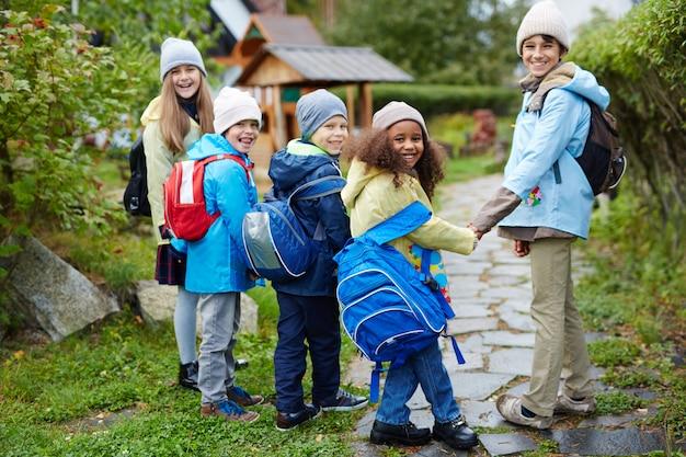 Grupo de crianças felizes, caminhando para a escola no outono