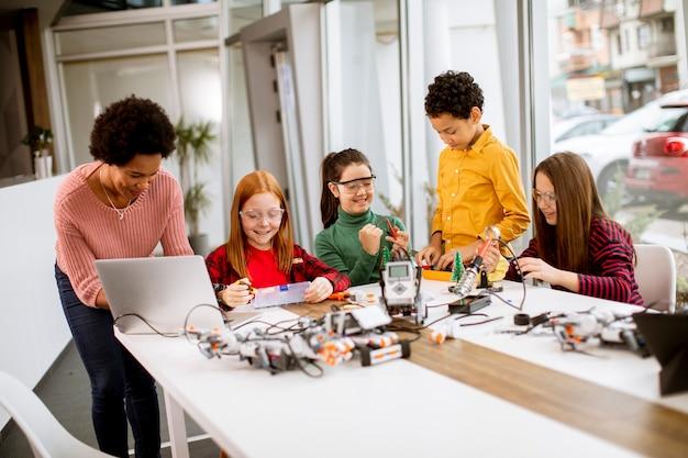 Grupo de crianças felizes com sua professora de ciências afro-americana com um laptop programando brinquedos elétricos e robôs na sala de aula de robótica