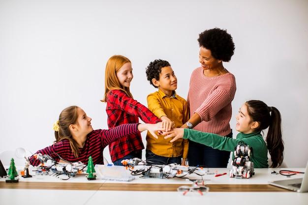 Grupo de crianças felizes com sua professora de ciências afro-americana programando brinquedos elétricos e robôs na sala de aula de robótica