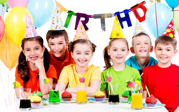 Grupo de crianças felizes em camisas coloridas, se divertindo na festa de aniversário - isolado em um branco.