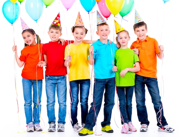 Grupo de crianças felizes em camisetas coloridas com balões em uma parede branca.