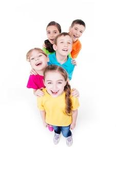 Grupo de crianças felizes em camisetas coloridas juntos. vista do topo. isolado no branco.