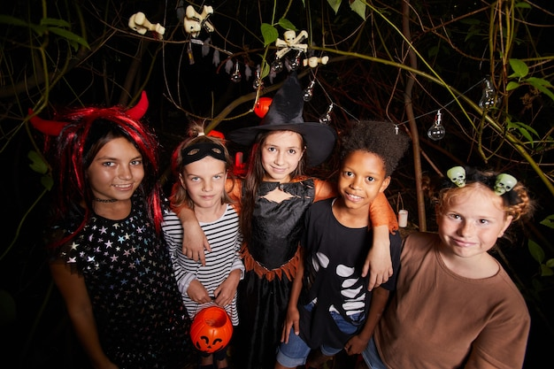 Grupo de crianças felizes em fantasias, sorrindo para a câmera e celebrando o halloween juntos na floresta escura