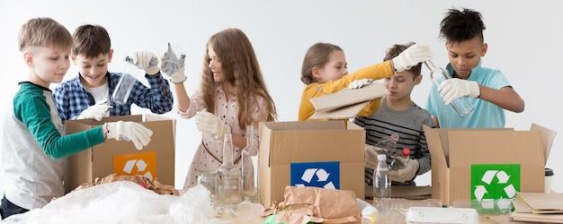 Grupo de crianças felizes em reciclar juntos