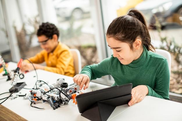 Grupo de crianças felizes programando brinquedos elétricos e robôs na sala de aula de robótica