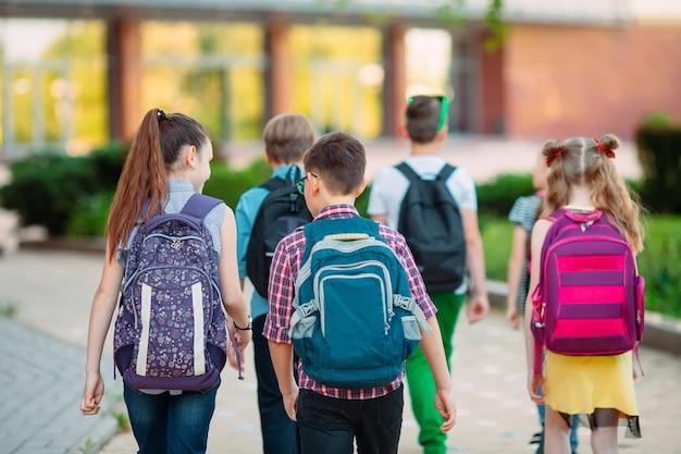Grupo de crianças indo para a escola juntos.