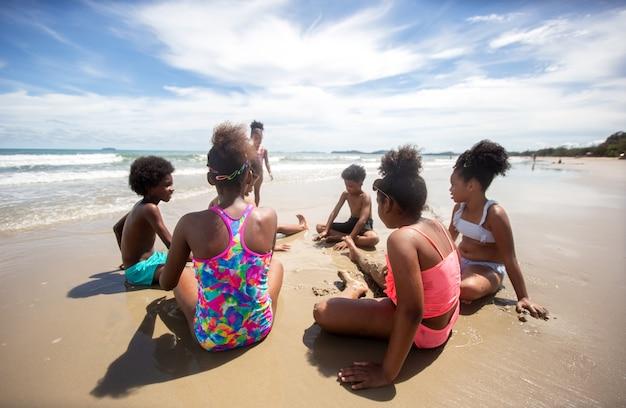 Grupo de crianças joga areia na praia