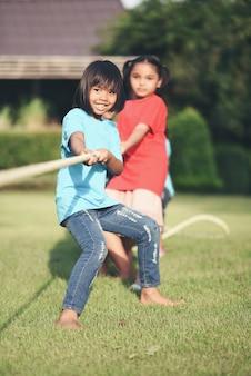 Grupo de crianças jogando cabo de guerra no parque