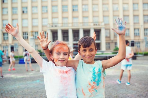 Grupo de crianças jogando pó colorido no ar. celebrações de holi. amigos se divertindo durante o holi fest. infância feliz. meninos pré-adolescentes brincando com cores. conceito para o festival indiano holi.