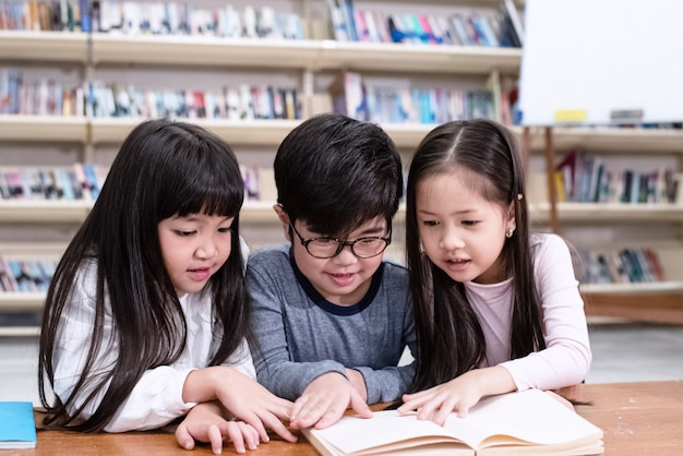 Grupo de crianças lendo livro, com sentimento interessado, na biblioteca, luz embaçada ao redor