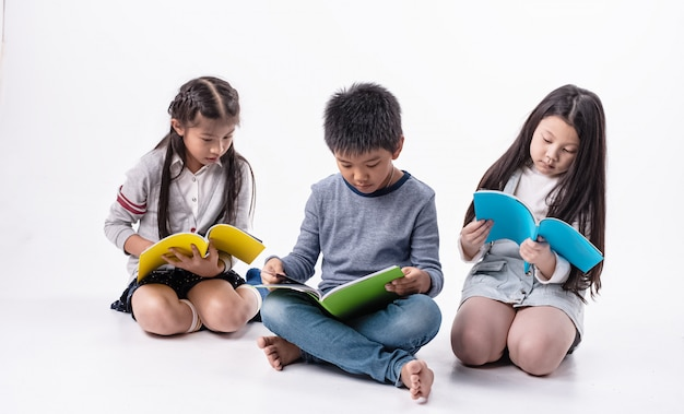 Grupo de crianças lendo livro juntos, com sentimento de interesse, fazendo atividade juntos
