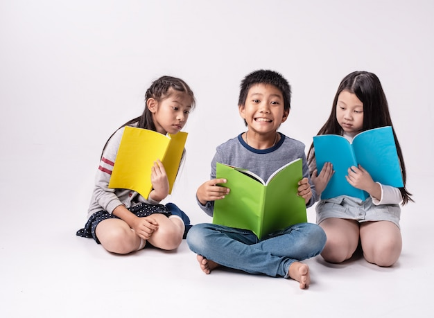 Grupo de crianças lendo livro togeter, com sentimento de interesse, fazendo atividade juntos