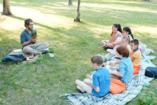 Grupo de crianças levantando as mãos enquanto estão sentadas na fileira na grama verde e respondendo a perguntas dos professores em aulas ao ar livre