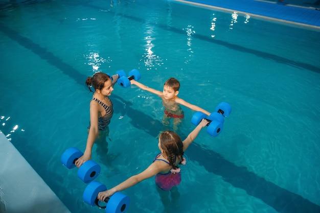 Grupo de crianças nadando, treino com halteres na piscina