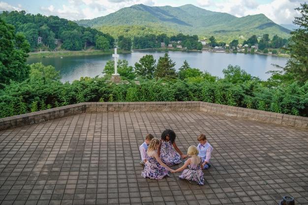 Grupo de crianças orando perto de uma cruz cercada por um lago e colinas cobertas de florestas