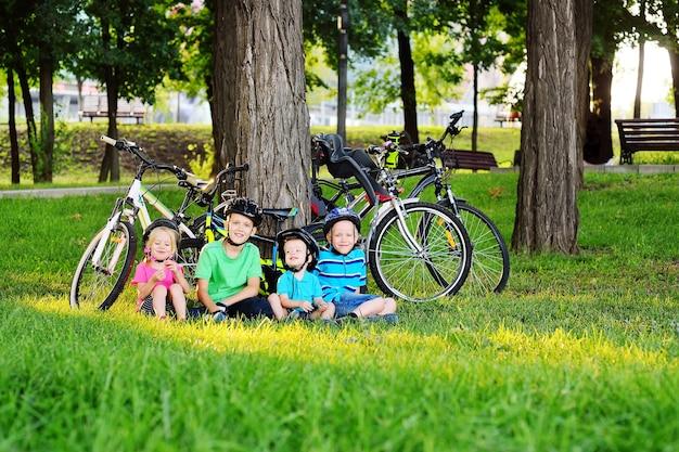 Grupo de crianças pequenas com roupas coloridas e capacetes de proteção para bicicletas