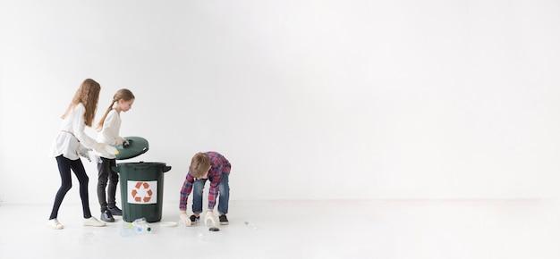 Grupo de crianças pequenas reciclagem juntos