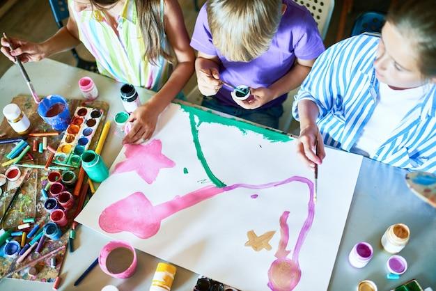 Grupo de crianças pintando imagens juntos na aula de arte