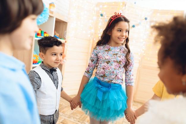 Grupo de crianças que dançam em volta da dança na festa de anos.