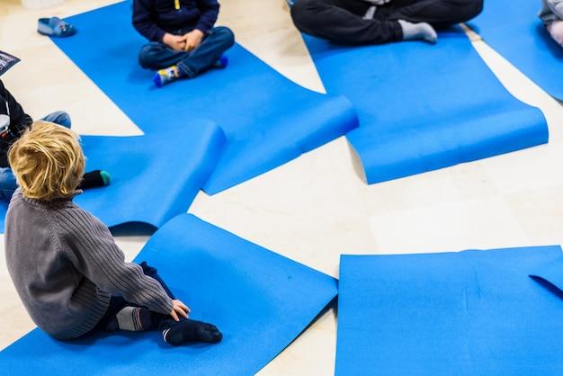Grupo de crianças que fazem exercícios da ioga e que relaxam em alguma esteira.