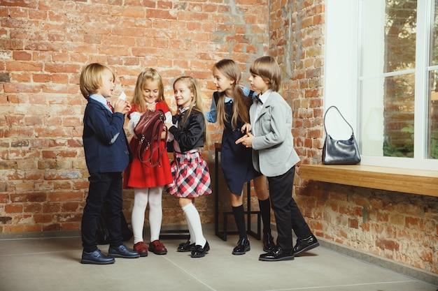 Grupo de crianças que passam um tempo juntos depois da escola. amigos bonitos descansando depois das aulas antes de começar a fazer a lição de casa. interior moderno do sotão. tempo escolar, amizade, educação, conceito de união.