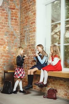 Grupo de crianças que passam um tempo juntos depois da escola. bonitos amigos descansando depois das aulas, antes de começar a fazer o dever de casa. interior moderno do sotão. tempo escolar, amizade, educação, conceito de união.