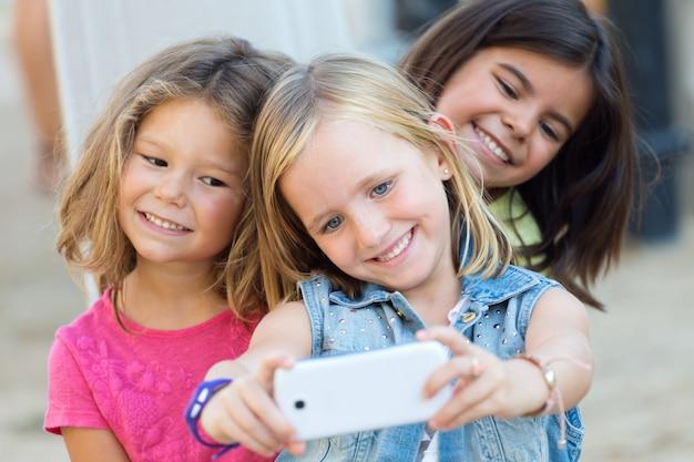 Grupo de crianças que tomam um selfie no parque.