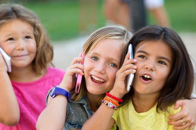 Grupo de crianças que usam telefones celulares no parque.