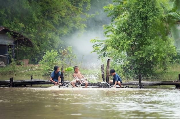 Grupo de crianças rurais sentado e jogando água juntos na ponte de madeira sobre o pântano