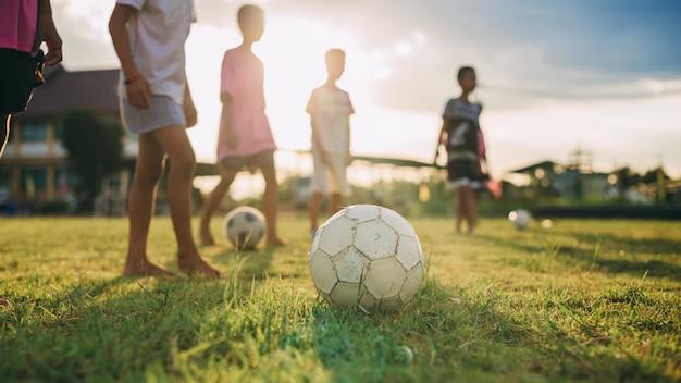 Grupo de crianças se divertindo jogando futebol de rua para exercício em área rural comunitária