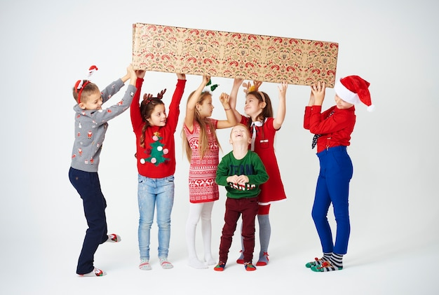 Grupo de crianças se preparando segurando uma grande caixa de presente
