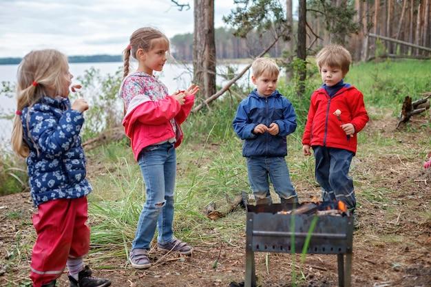 Grupo de crianças sentadas perto do fogo e se preparando para assar doces de marshmallow na fogueira, caminhada no fim de semana, viagens locais após o confinamento, estadia