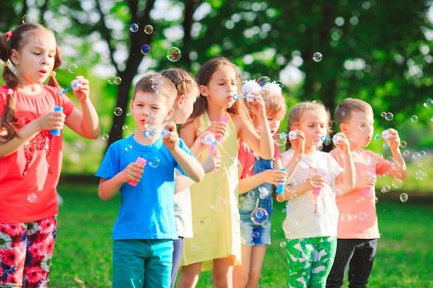 Grupo de crianças soprando bolhas de sabão