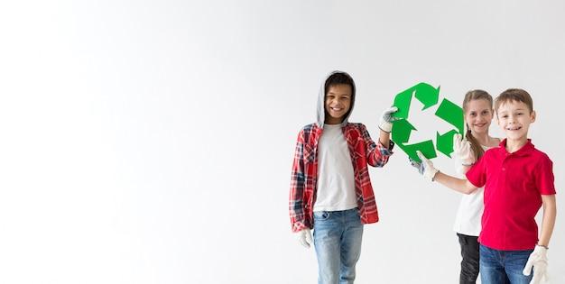 Grupo de crianças sorridente segurando placa reciclar