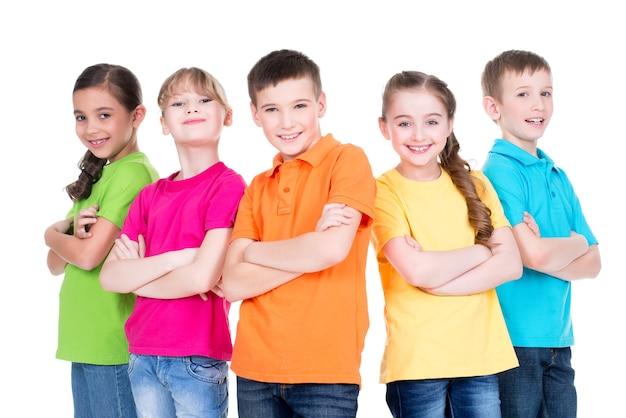 Grupo de crianças sorridentes com os braços cruzados em camisetas coloridas que estão juntos no fundo branco.