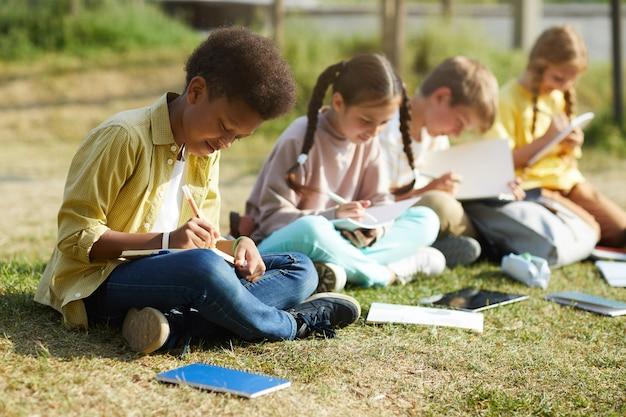 Grupo de crianças sorridentes, estudando ao ar livre, sentados em fileira na grama verde e escrevendo em livros didáticos, foco no garoto afro-americano em primeiro plano, copie o espaço