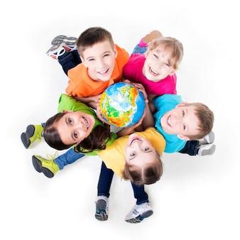 Grupo de crianças sorridentes, sentadas no chão em um círculo com um globo nas mãos - isolado no branco.