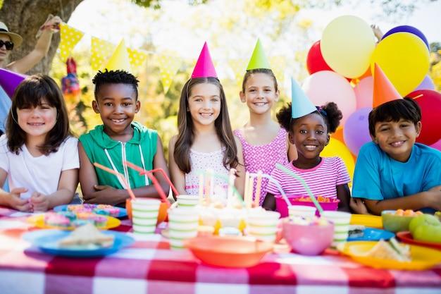 Grupo de crianças sorrindo e posando durante uma festa de aniversário
